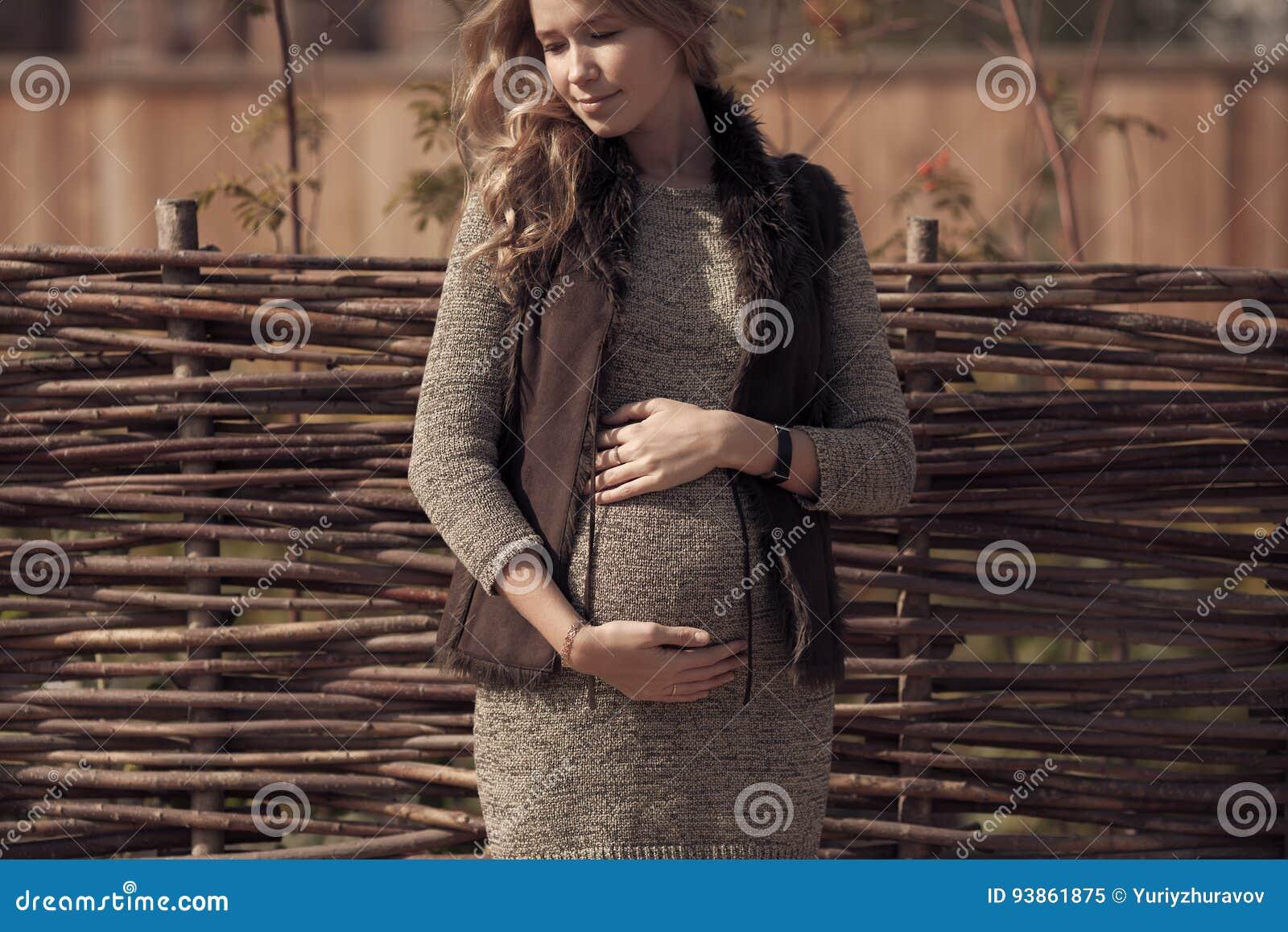 Attraktiv gravid kvinna i slags tvåsittssoffakläder på bygd