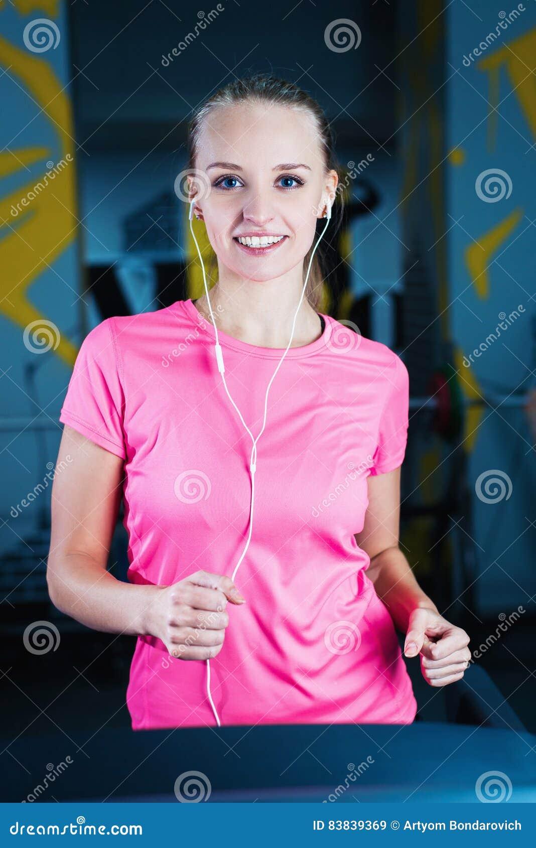 Attraktiv konditionflickaspring på maskintrampkvarnen Nätt flicka som gör genomkörare på den moderna konditionidrottshallen