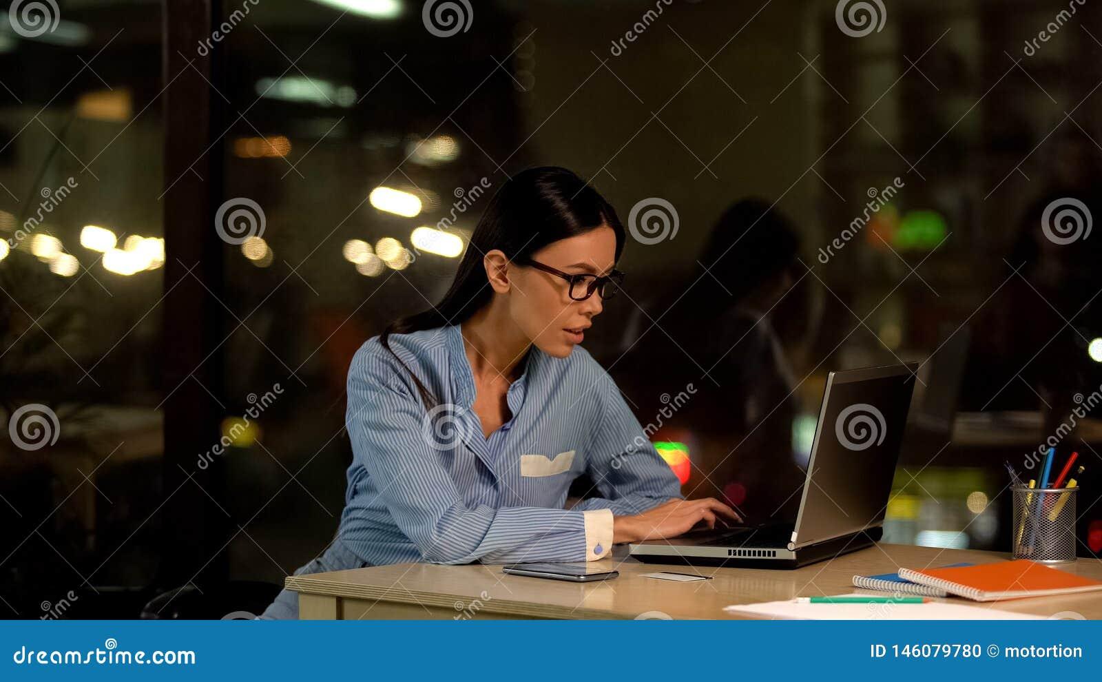 Attraktiv kontorsarbetare som skriver p? b?rbara datorn p? natten, internetforskning, jobb