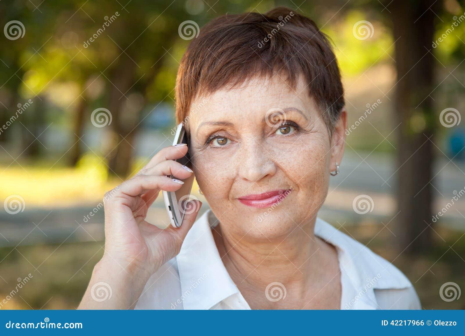 50 år kvinna Attraktiv Kvinna 50 år Med En Mobiltelefon Arkivfoto   Bild av  50 år kvinna