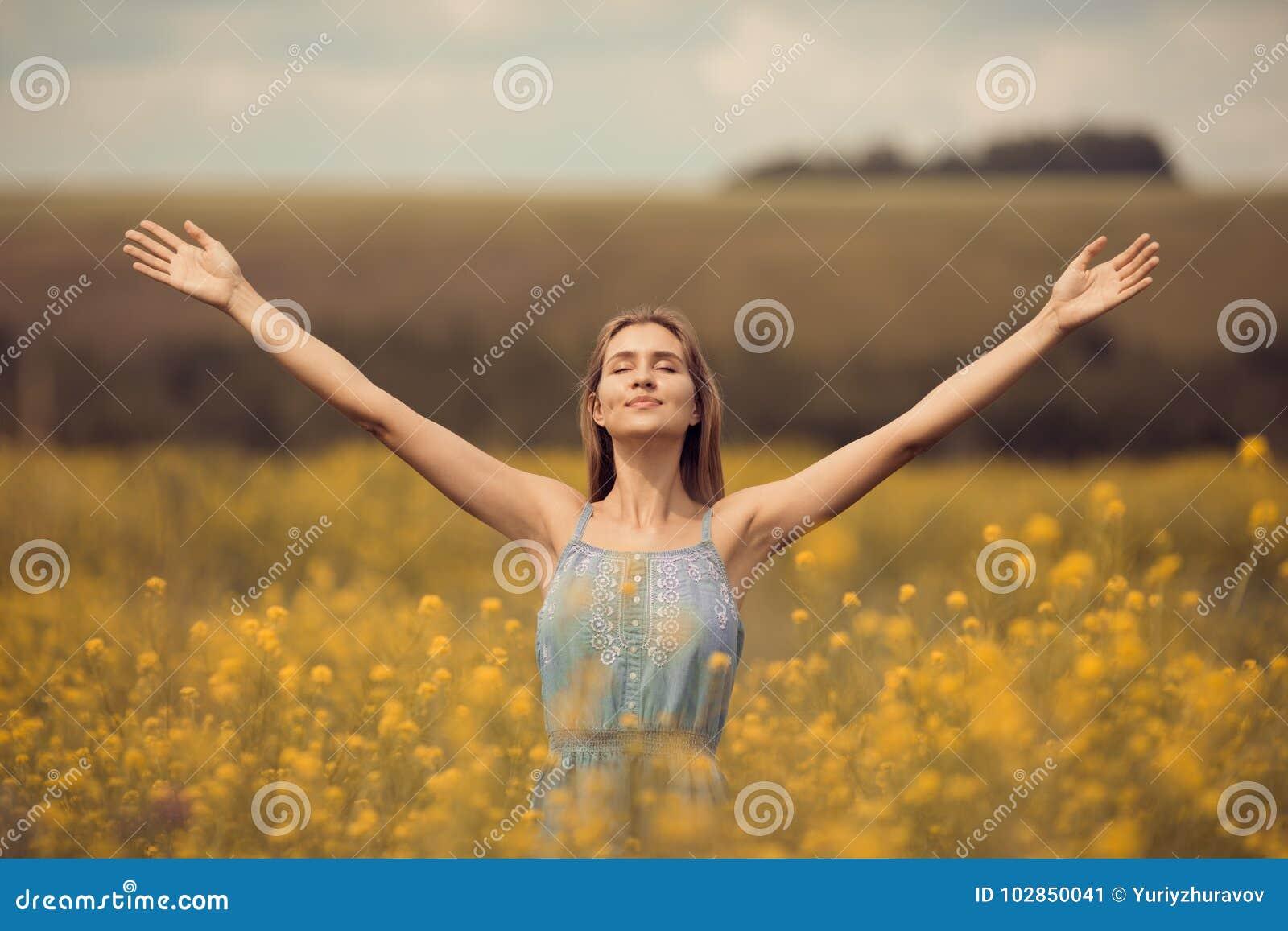 Attraktiv kvinna i klänning på blommafältet