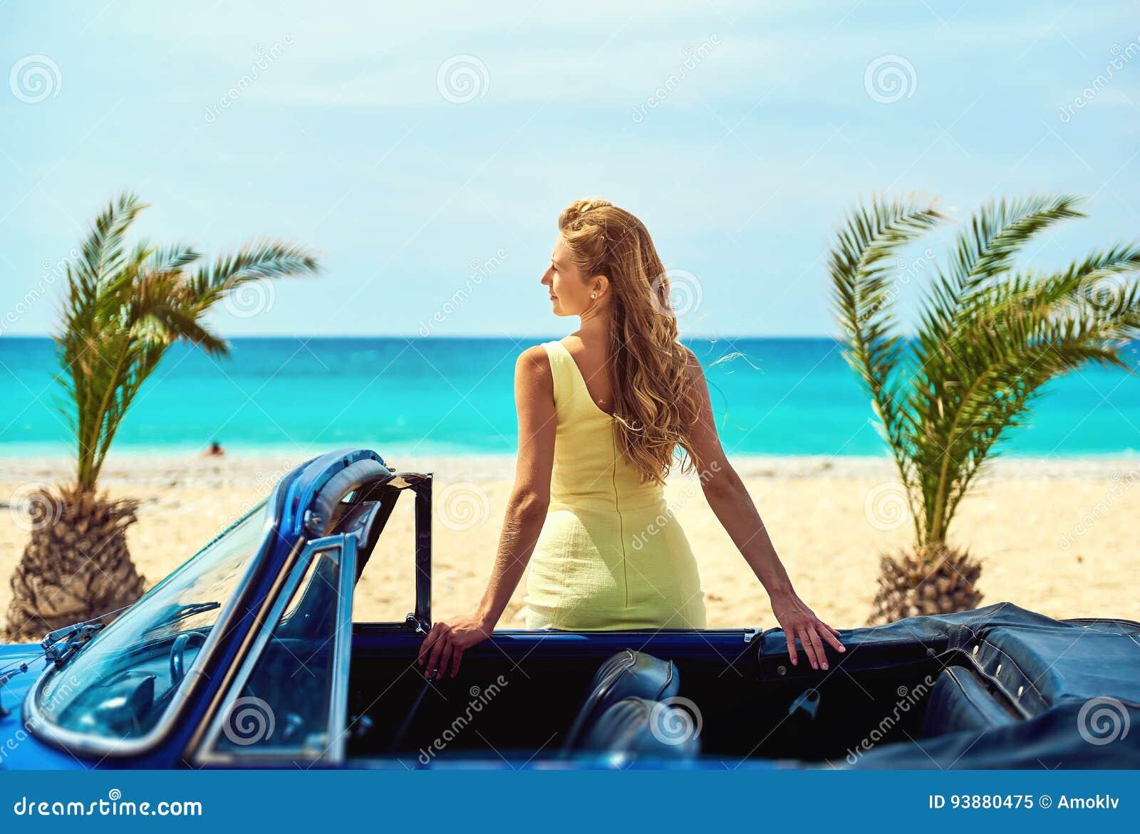Attraktiv kvinna nära den retro bilen på den tropiska stranden