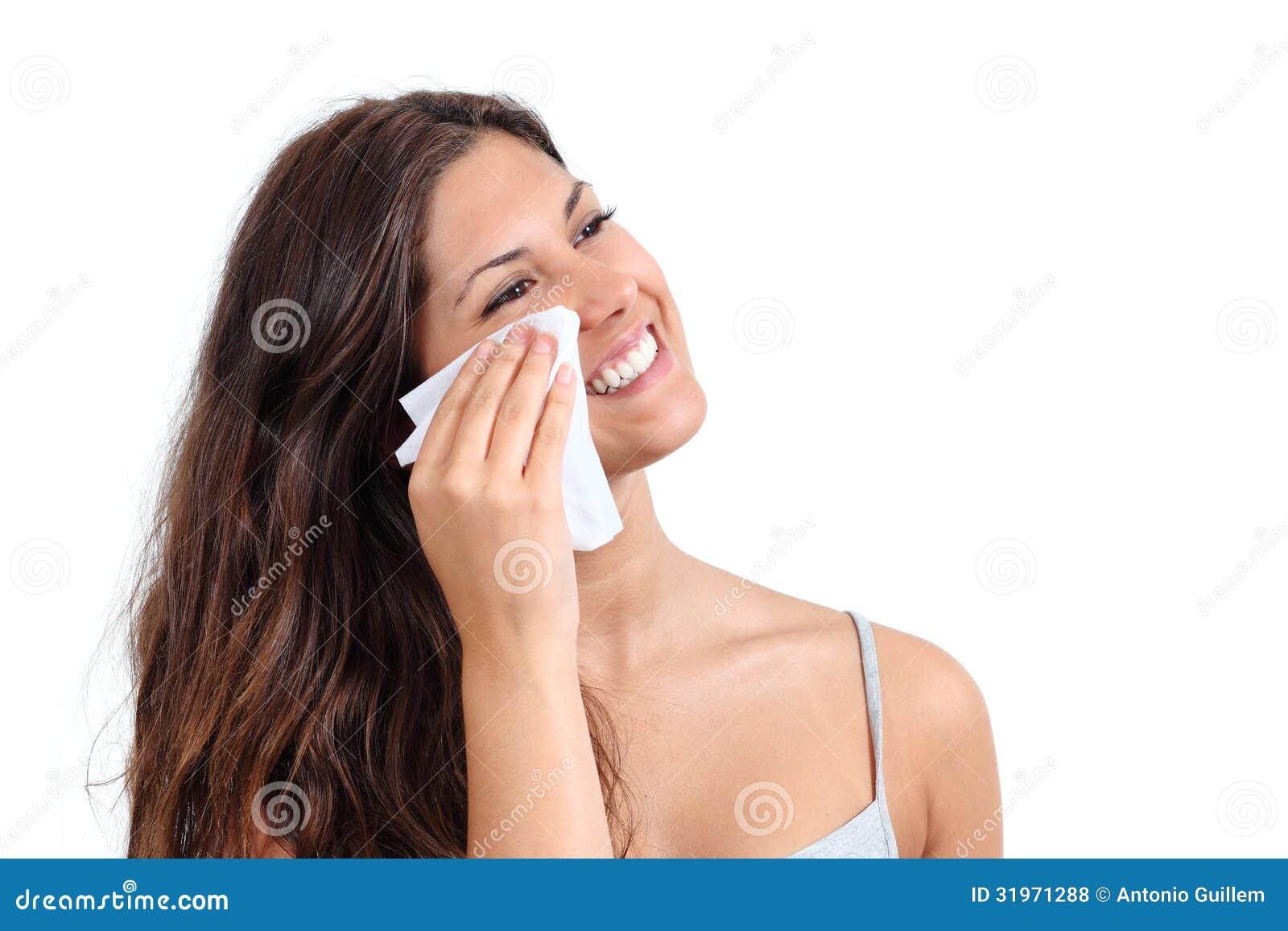 Attraktiv kvinna som gör ren hennes framsida med ett silkespapper