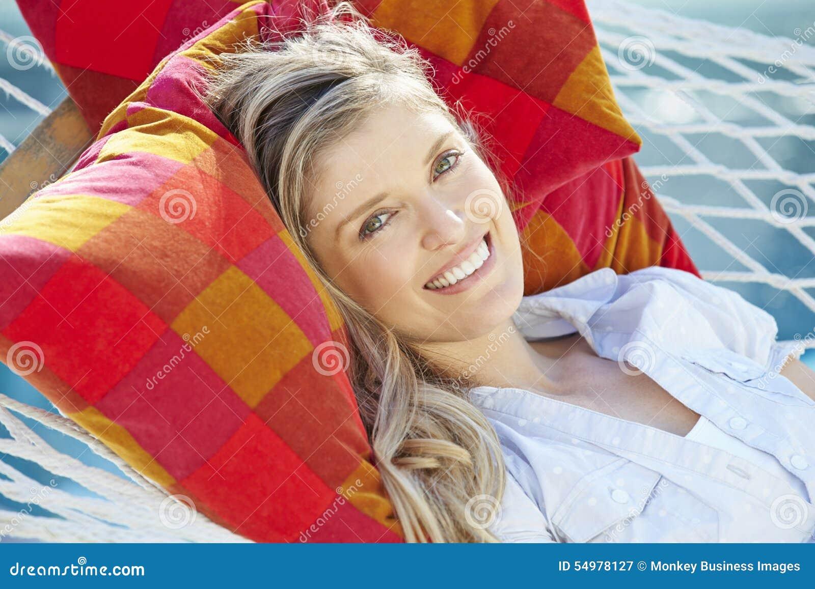 Attraktiv kvinna som kopplar av i trädgårds- hängmatta