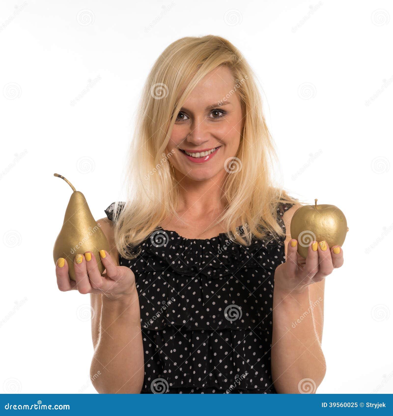 Attraktiv kvinna som rymmer ett guld- päron och äpple