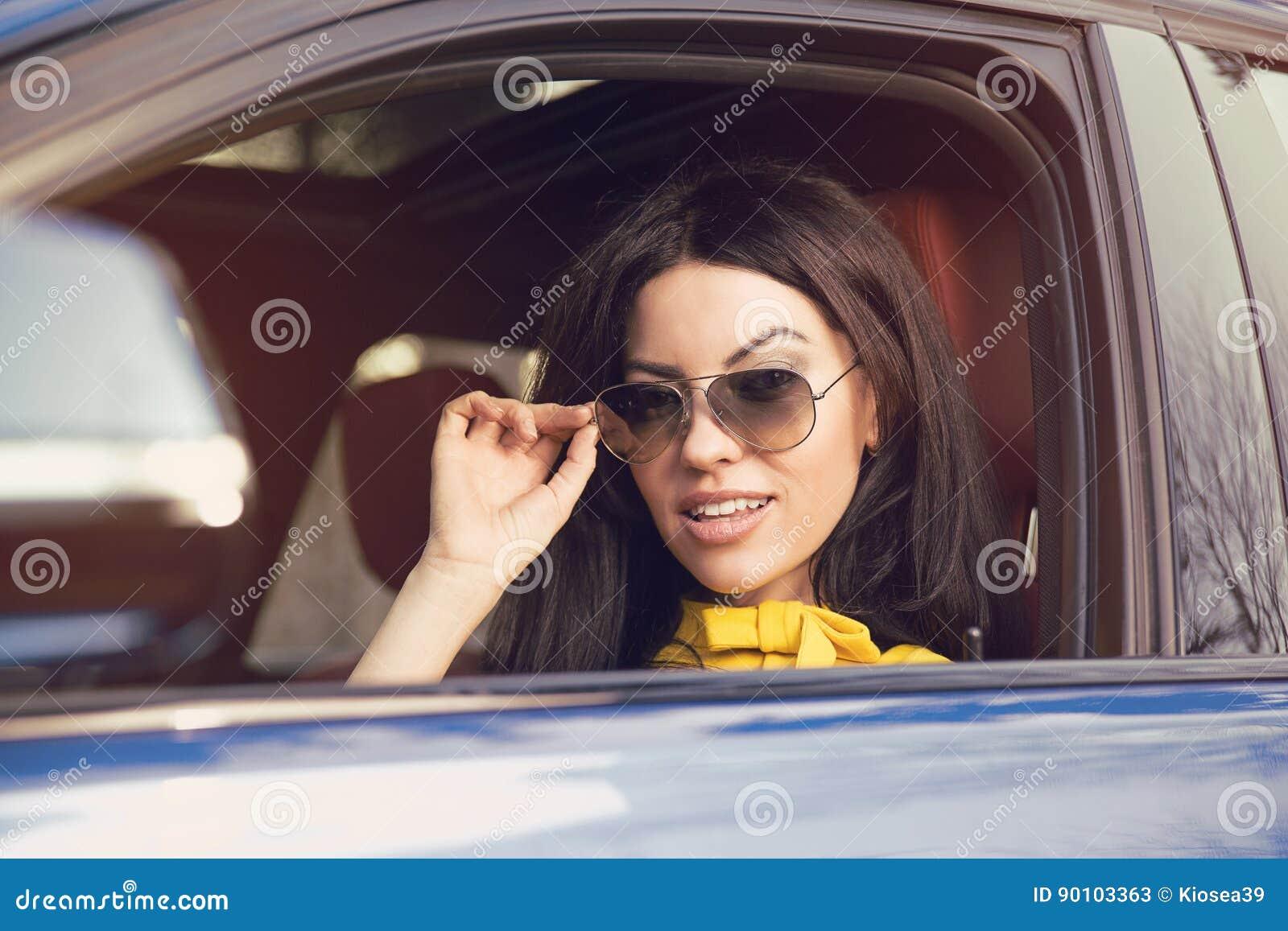 Attraktiv kvinnachaufför med solglasögon som sitter inom hennes bil