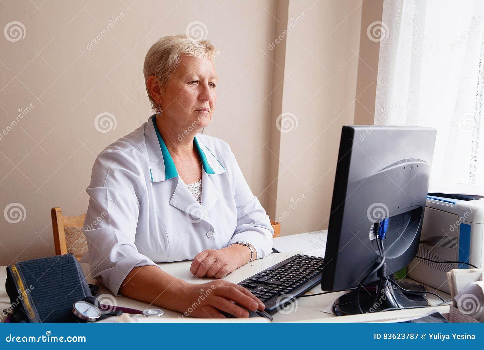 Attraktiv kvinnlig doktor som arbetar på hennes dator i hennes kontor