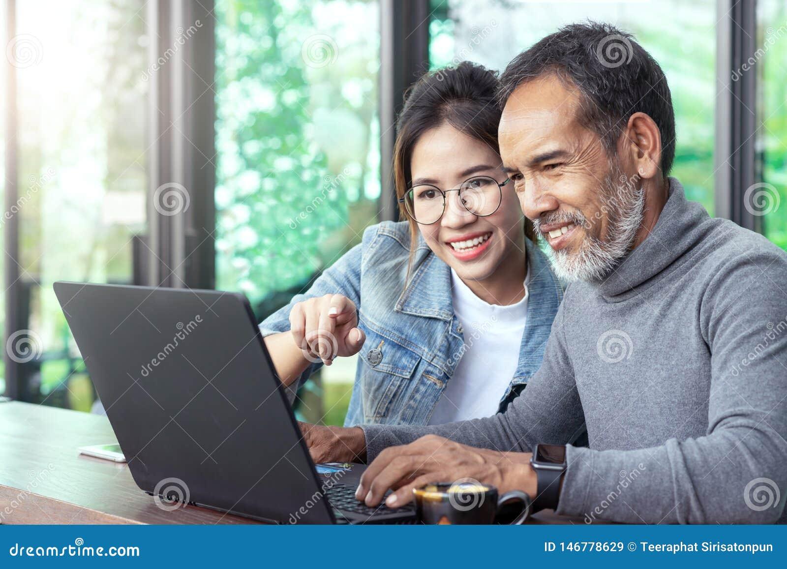 Attraktiv mogen asiatisk man med det vita stilfulla korta skägget som ser bärbar datordatoren med den tonårs- kvinnan för ögonexp