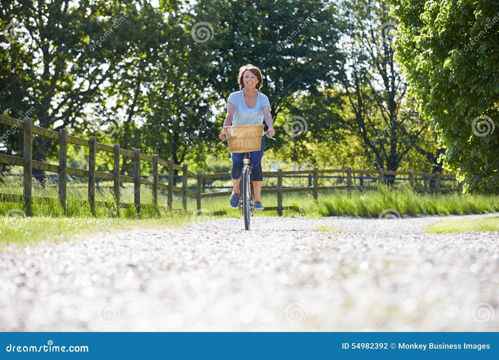 Attraktiv mogen kvinnaridningcykel längs landsgränd