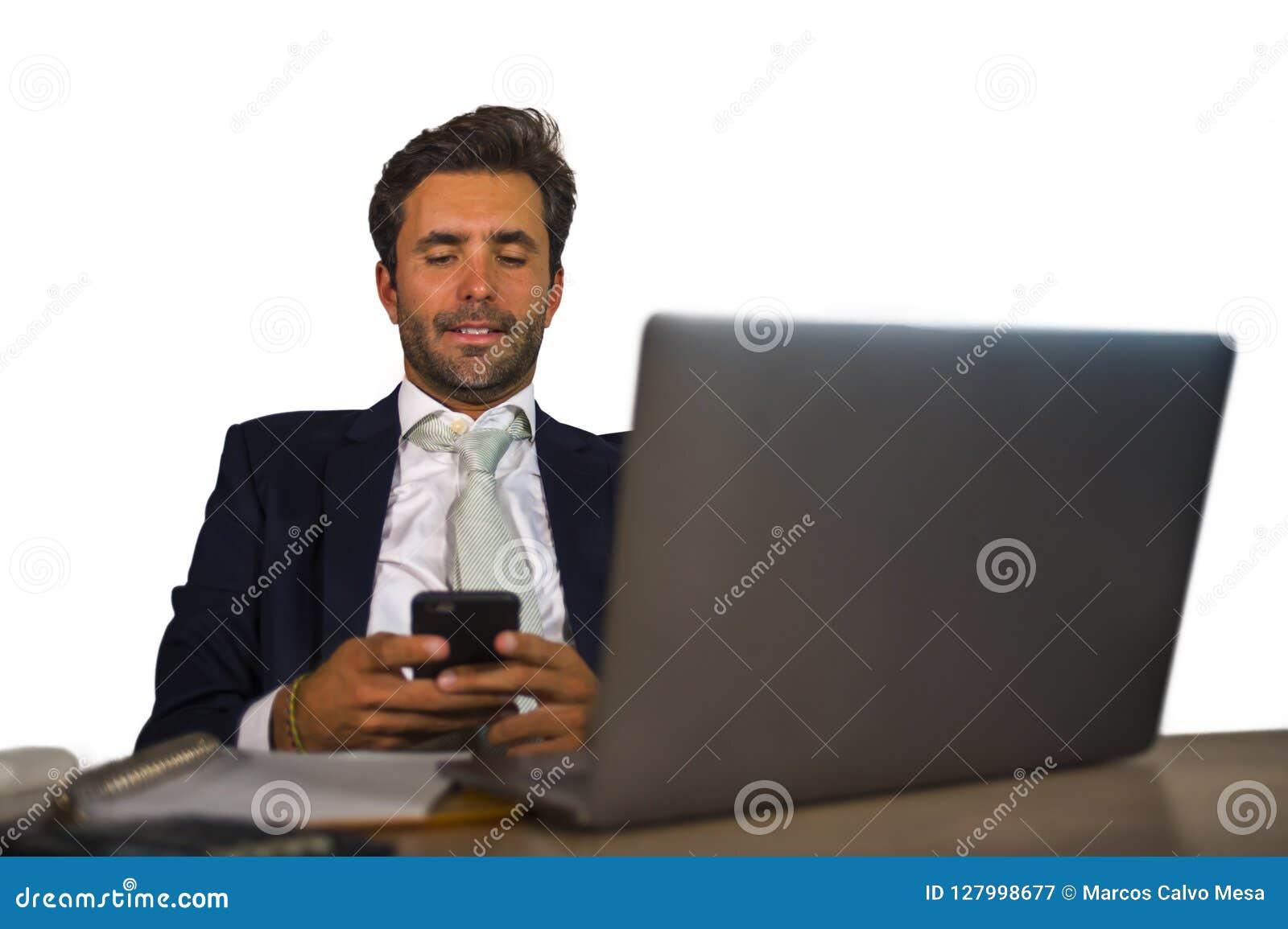 Attraktiv och effektiv affärsman som arbetar på skrivbordet för kontorsbärbar datordator som är säkert, i att le den lyckliga anv