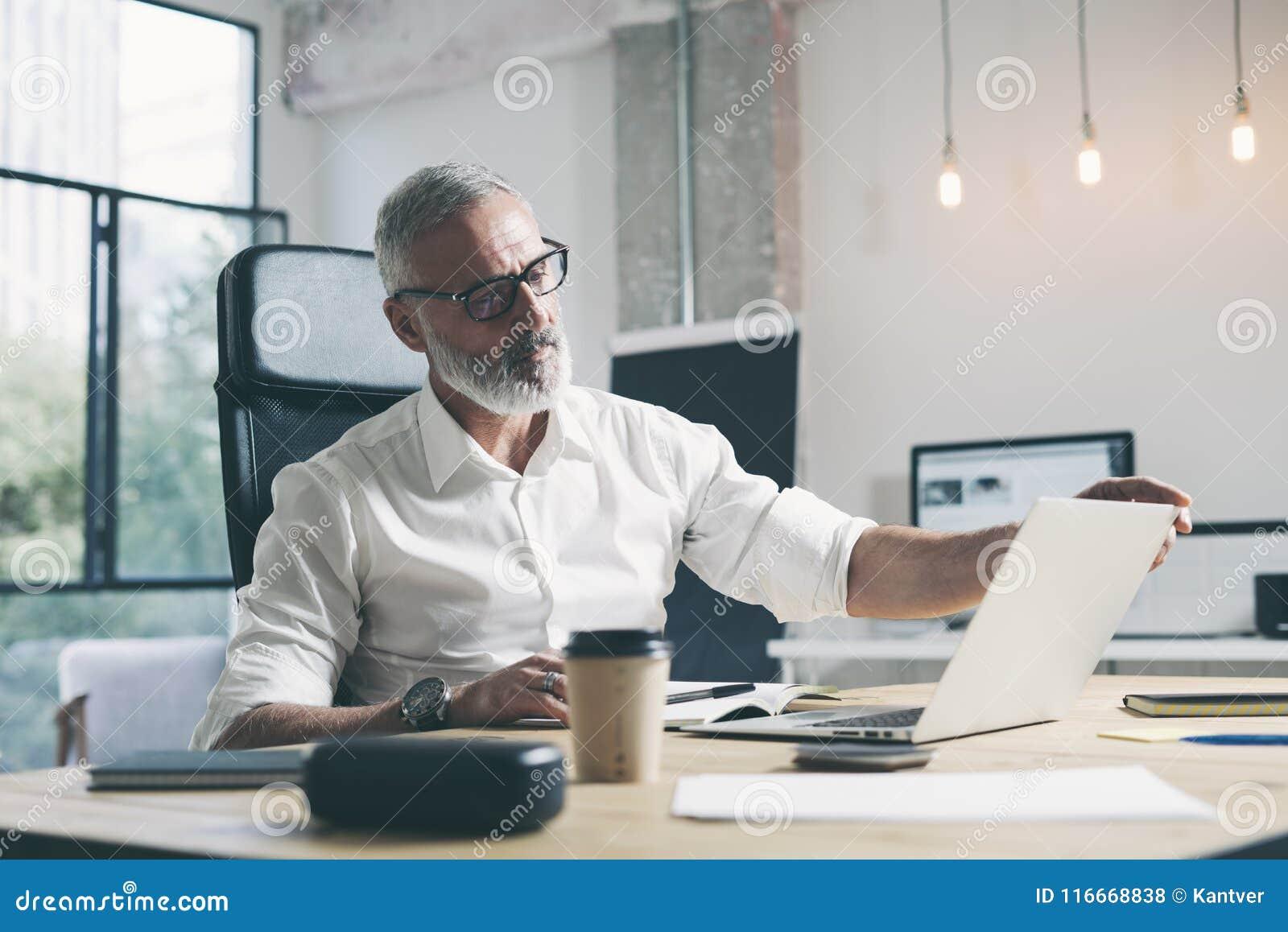 Attraktiv och förtrolig vuxen affärsman som använder den mobila bärbar datordatoren, medan arbeta på trätabellen på modernt