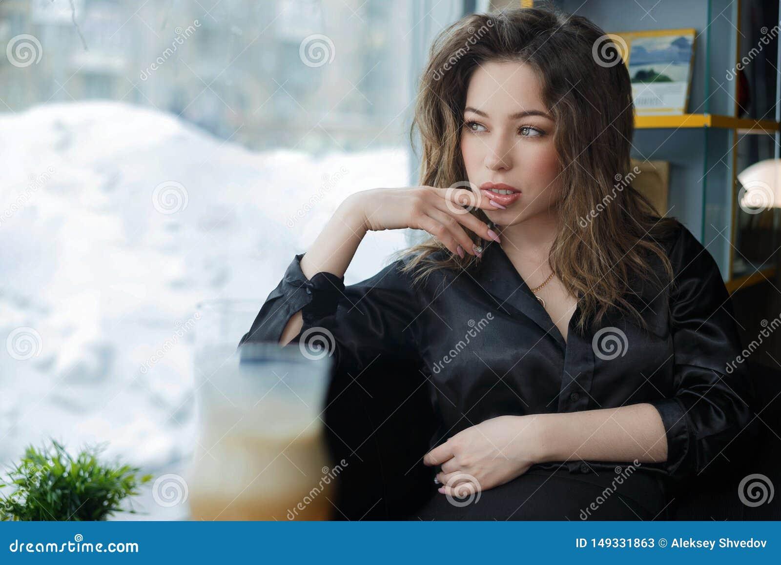 Attraktiv och gladlynt ung kvinna som ler i kaf?