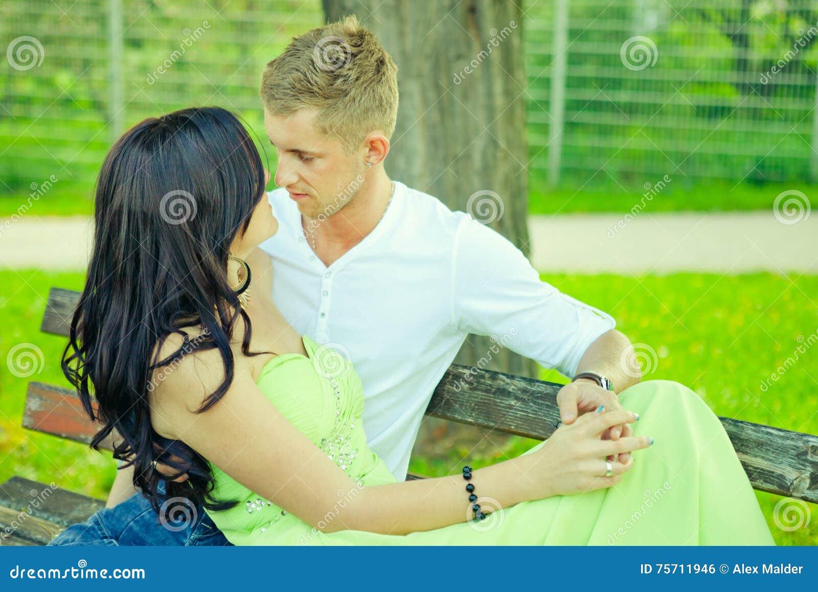 Attraktiv sitzen der Kerl mit dem Mädchen und umfassen auf einer Bank