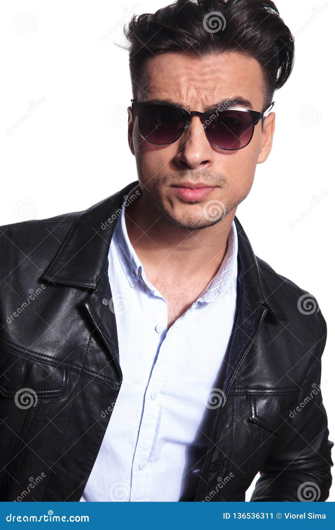 Attraktiv smart tillfällig man i läderomslaget som bär röd solglasögon