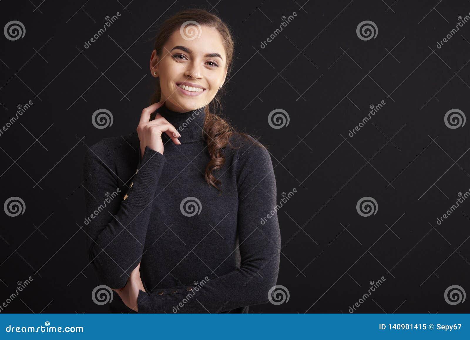 Attraktiv studiostående för ung kvinna, medan stå på mörk bakgrund