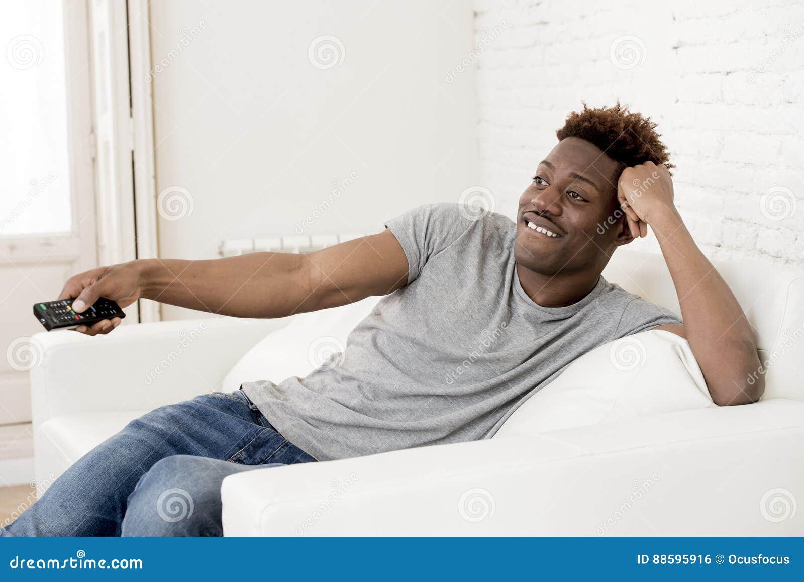 Attraktiv svart afrikansk amerikanman som sitter hållande ögonen på television för hemmastadd soffasoffa