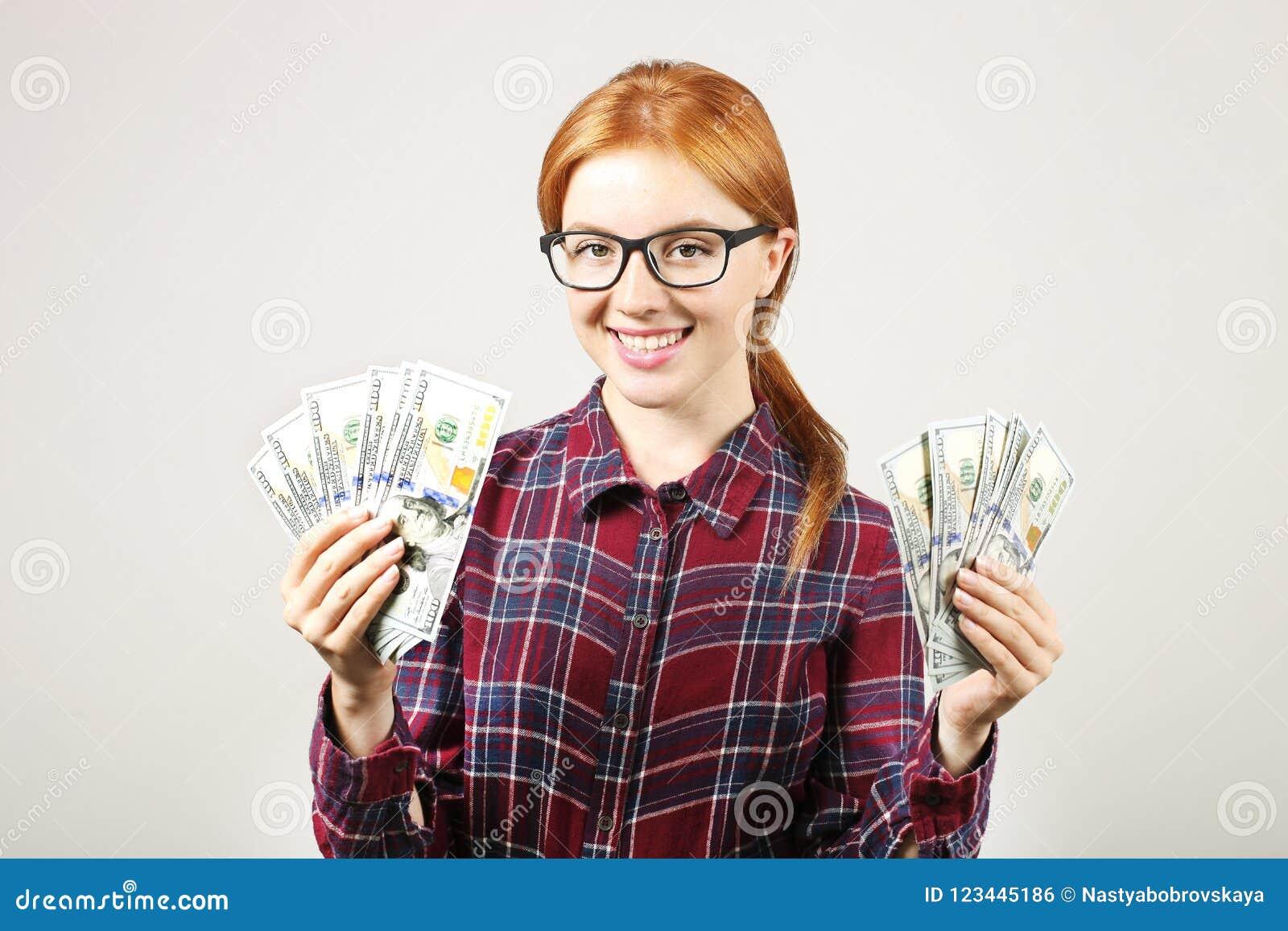 Attraktiv ung affärskvinna som poserar med gruppen av händer för USD kassa som in visar positiva sinnesrörelser och lyckligt ansi