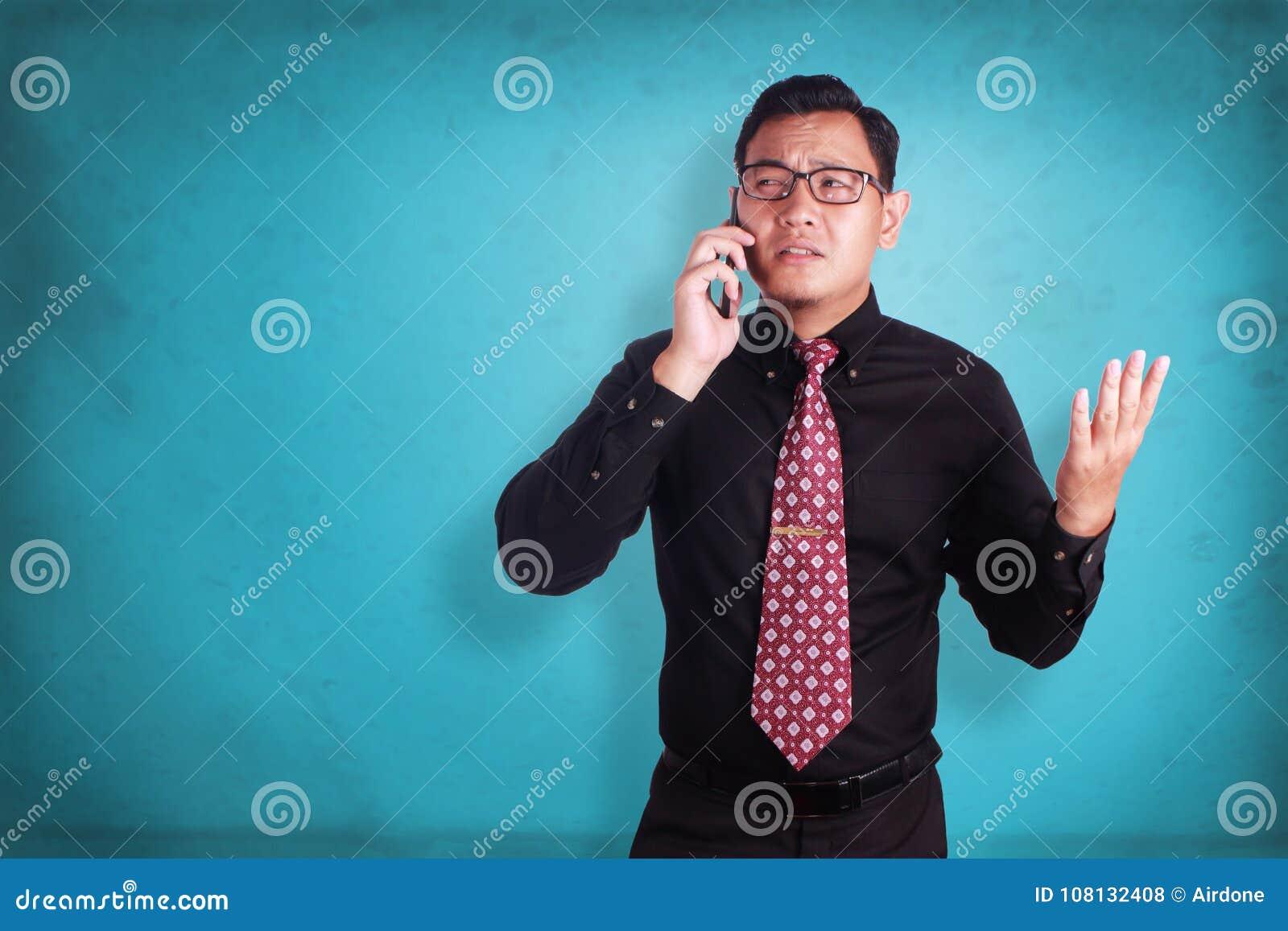 Attraktiv ung affärsman som talar på hans telefon