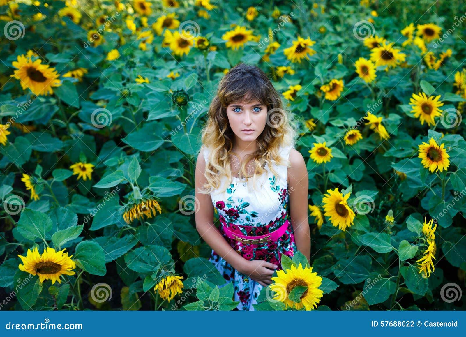 Attraktiv ung flicka i fältet av solrosor