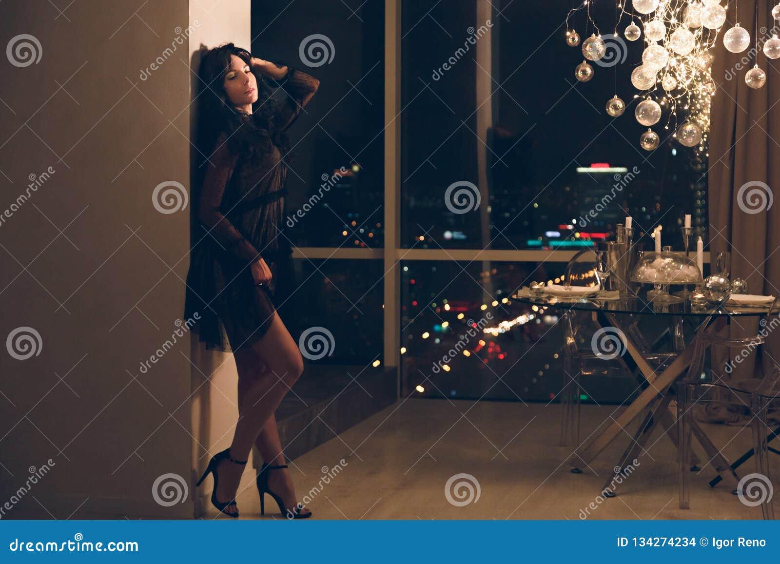 Attraktiv ung kvinna i den svarta coctailklänningen som lutar på väggen i hotellrum