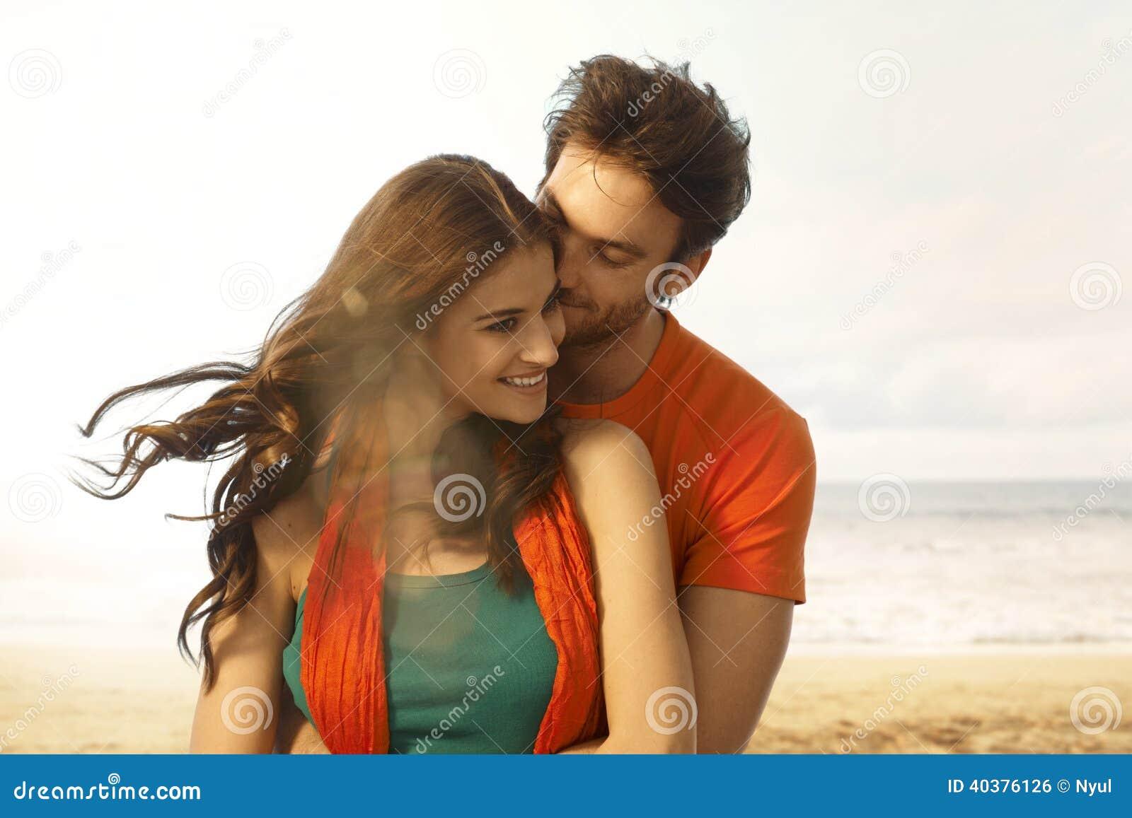 Attraktiv ung kvinna som får en kyss på stranden