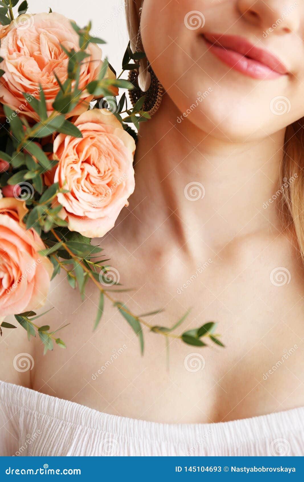 Attraktiv ung kvinna som poserar ?ver gr? bakgrund med blommor