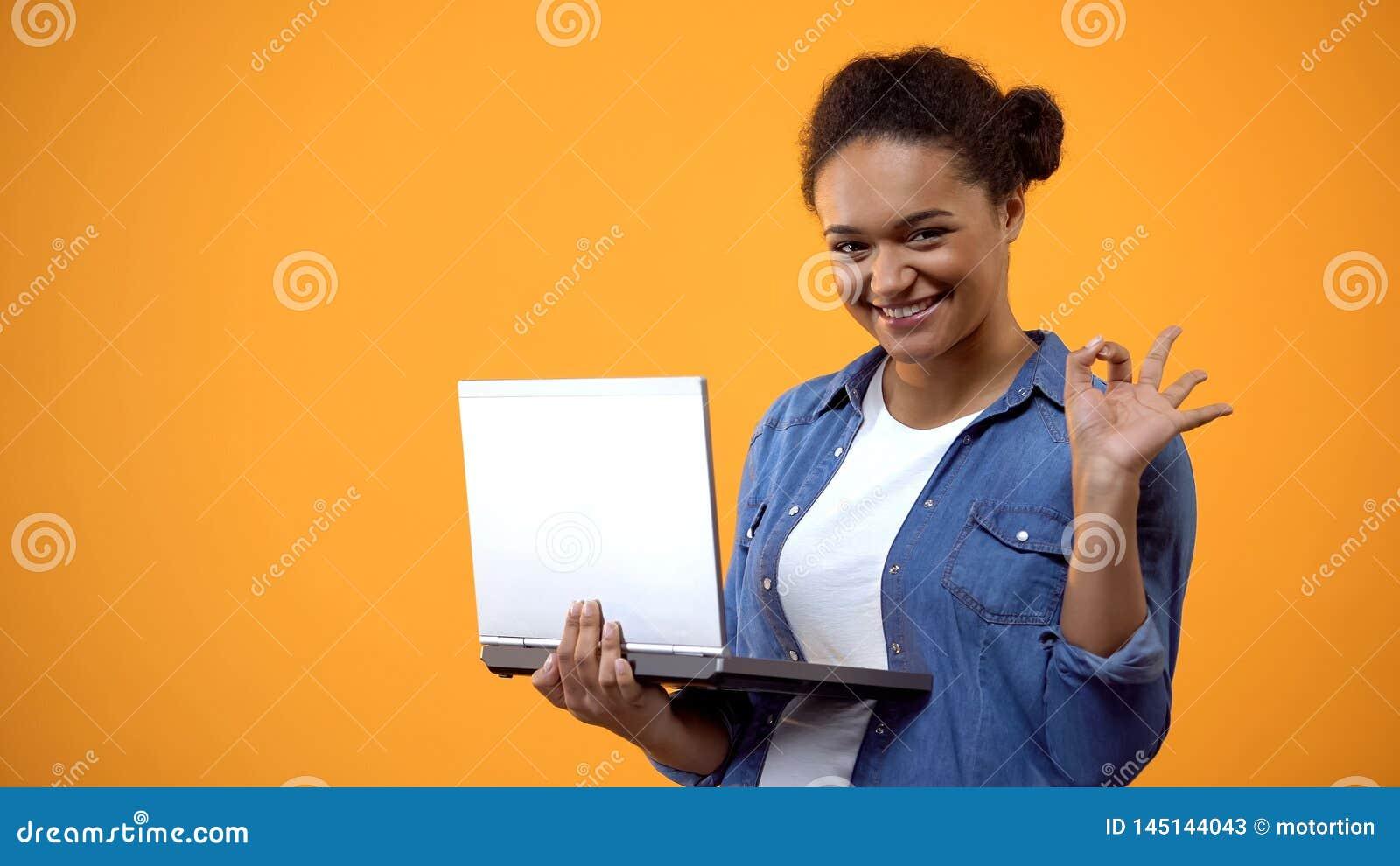 Attraktiv ung kvinnlig bärbar datorhand som visar det ok tecknet som tillfredsställs med anslutning