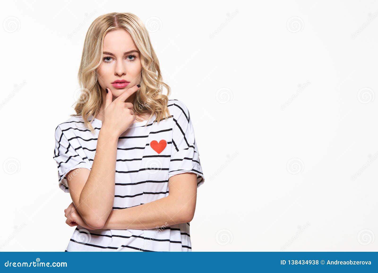 Attraktiv ung säker kvinna som bär tillfällig kläder som tänker, med handen på hakan som ser kameran