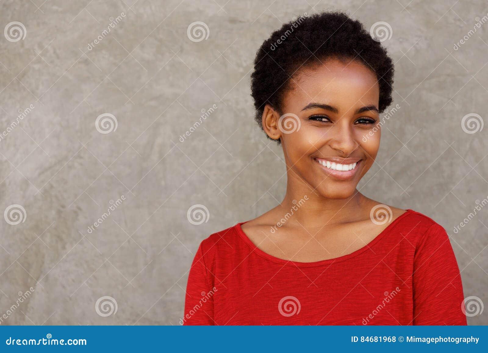 Attraktiv ung svart kvinna i rött le för skjorta
