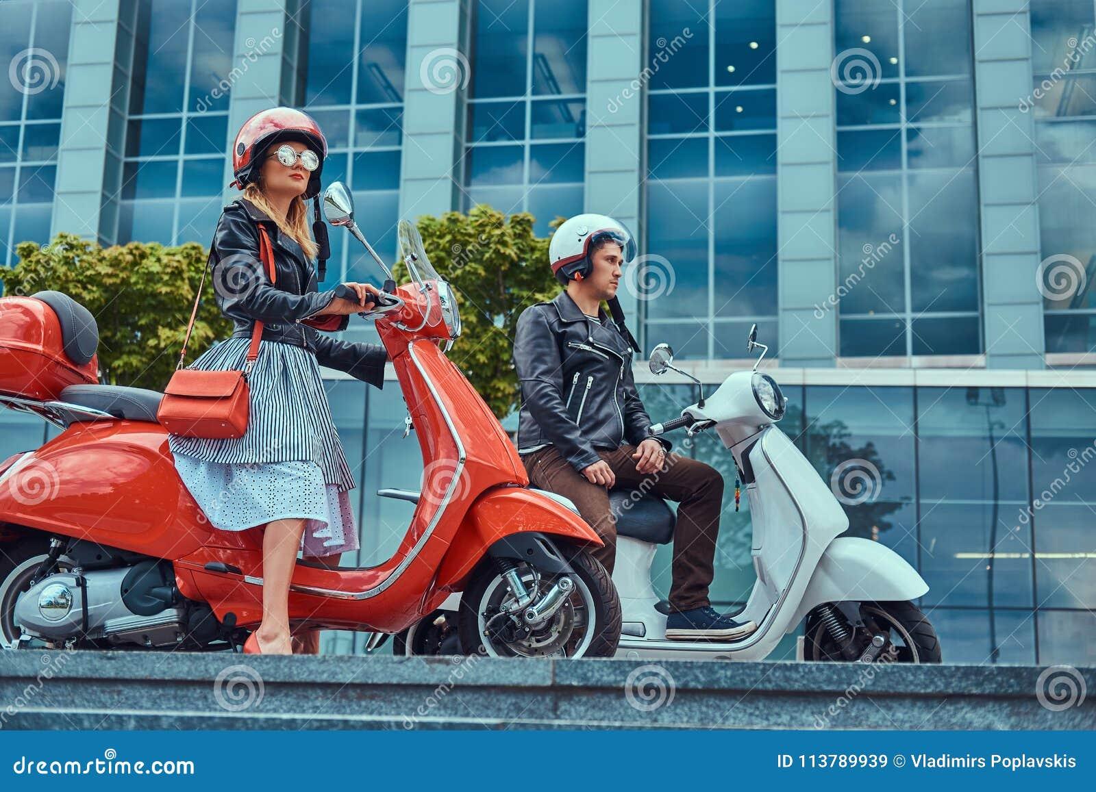 Attraktiva romantiska par, en stilig man och sexig kvinnlig som sitter på retro italienska sparkcyklar mot en skyskrapa