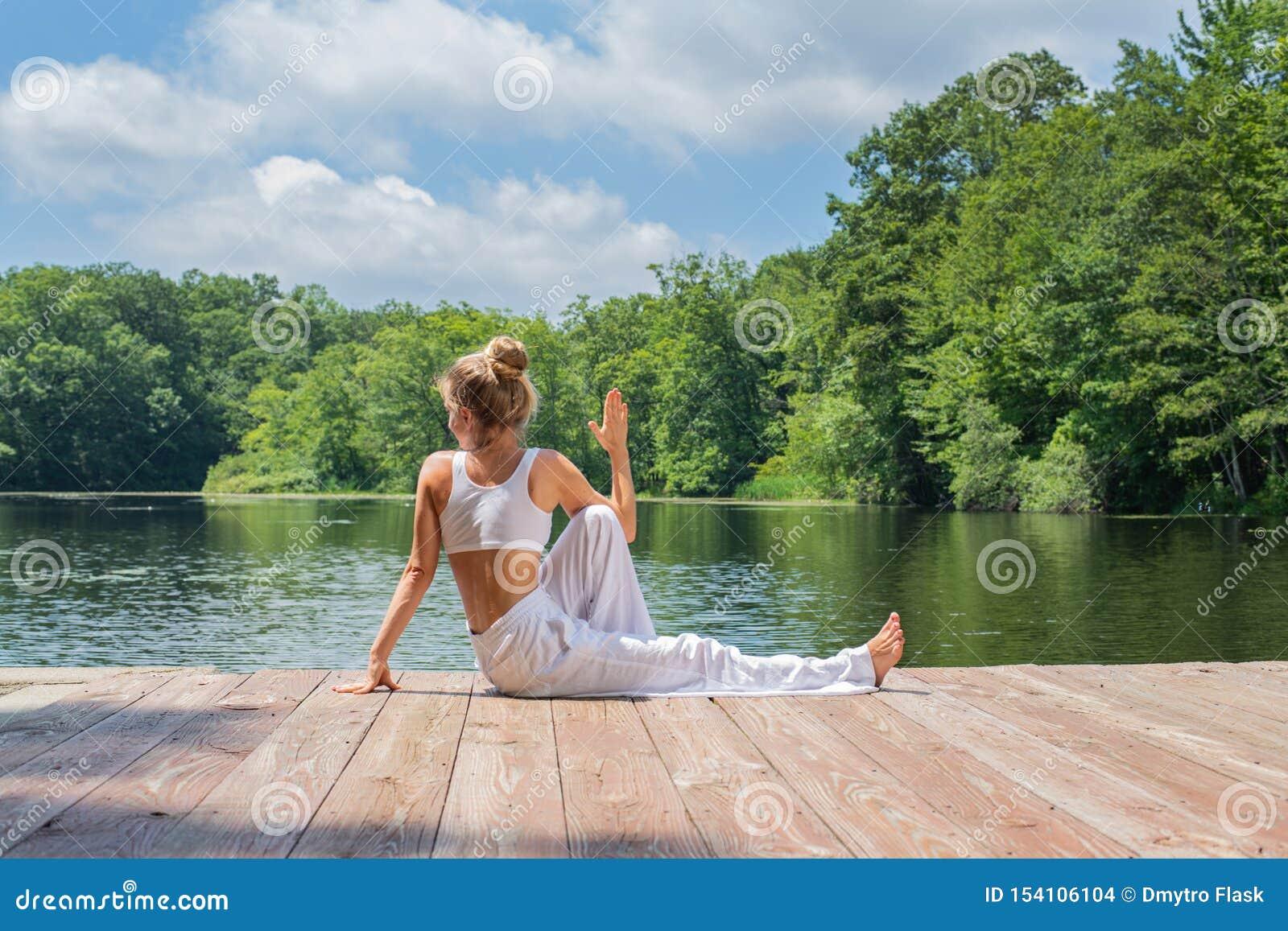 Attraktive Frau übt das Yoga, das in Haltung Ardha Matsyendrasana nahe See am Morgen sitzt