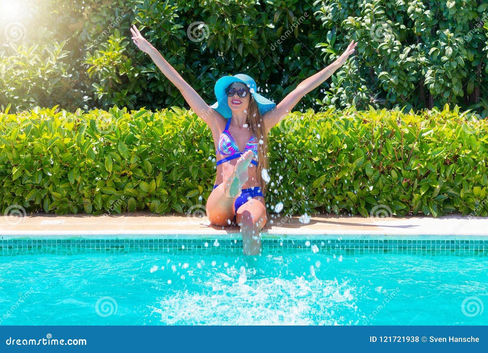 Attraktive Frau im Bikini hat Spaß am Poolside