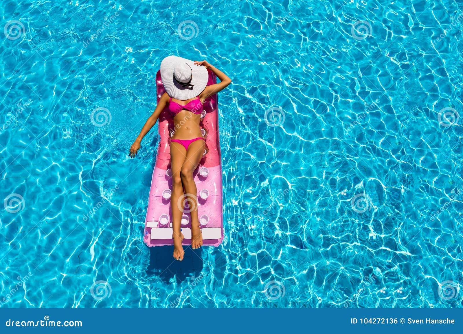 Attraktive Frau ist auf einer sich hin- und herbewegenden Matratze in einem Pool entspannend