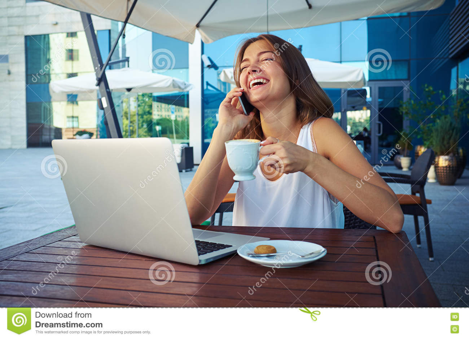 Attraktive Frau mit Tasse Kaffee lachend bei der Unterhaltung auf t