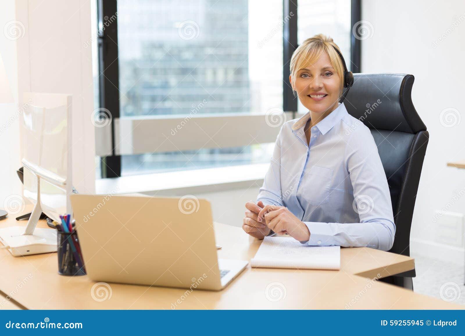 Attraktive Geschäftsfrau, die an Laptop arbeitet kopfhörer Gebäude b