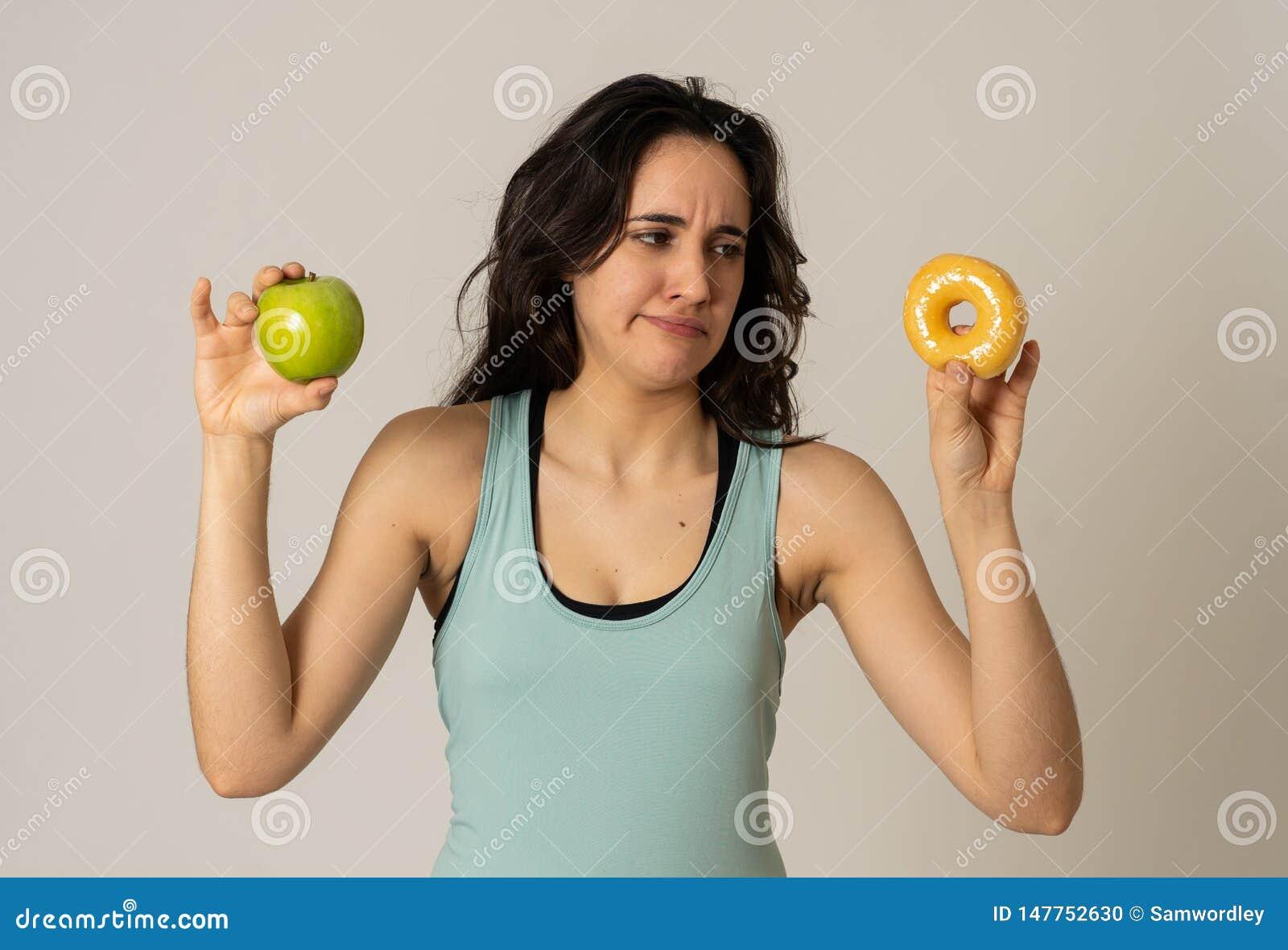 Attraktive junge Frau auf Di?t, die zwischen einem Apfel und einem Donut entscheidet