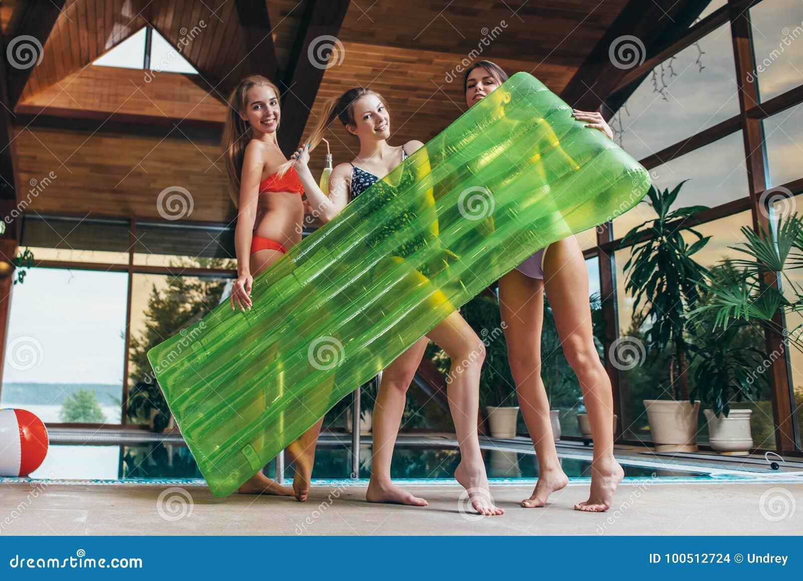 Attraktive lächelnde dünne Freundinnen, welche die Badeanzüge halten den aufblasbaren Aufenthaltsraum aufwirft in Badekurort und
