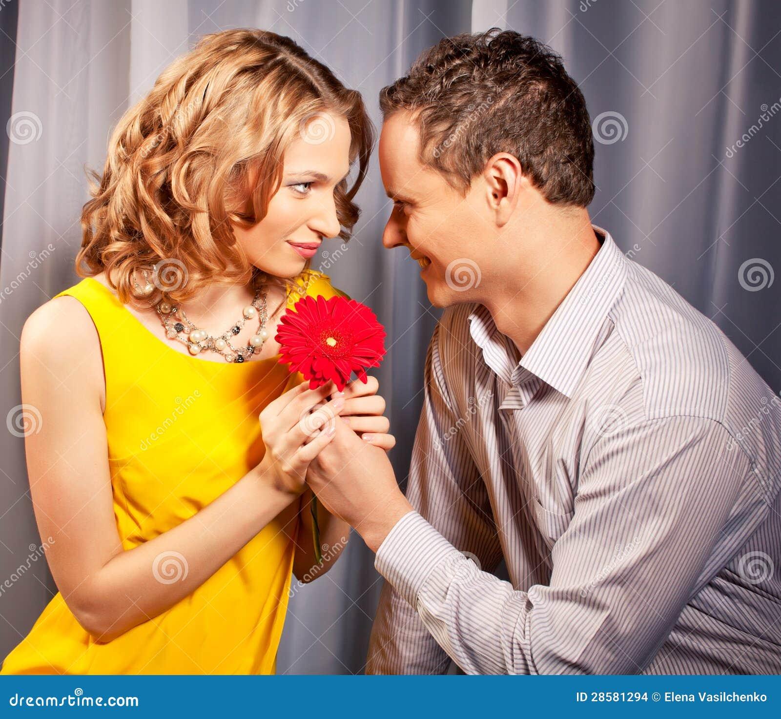 Attraktive Paare der Liebhaber. Mann stellt Blume dar.