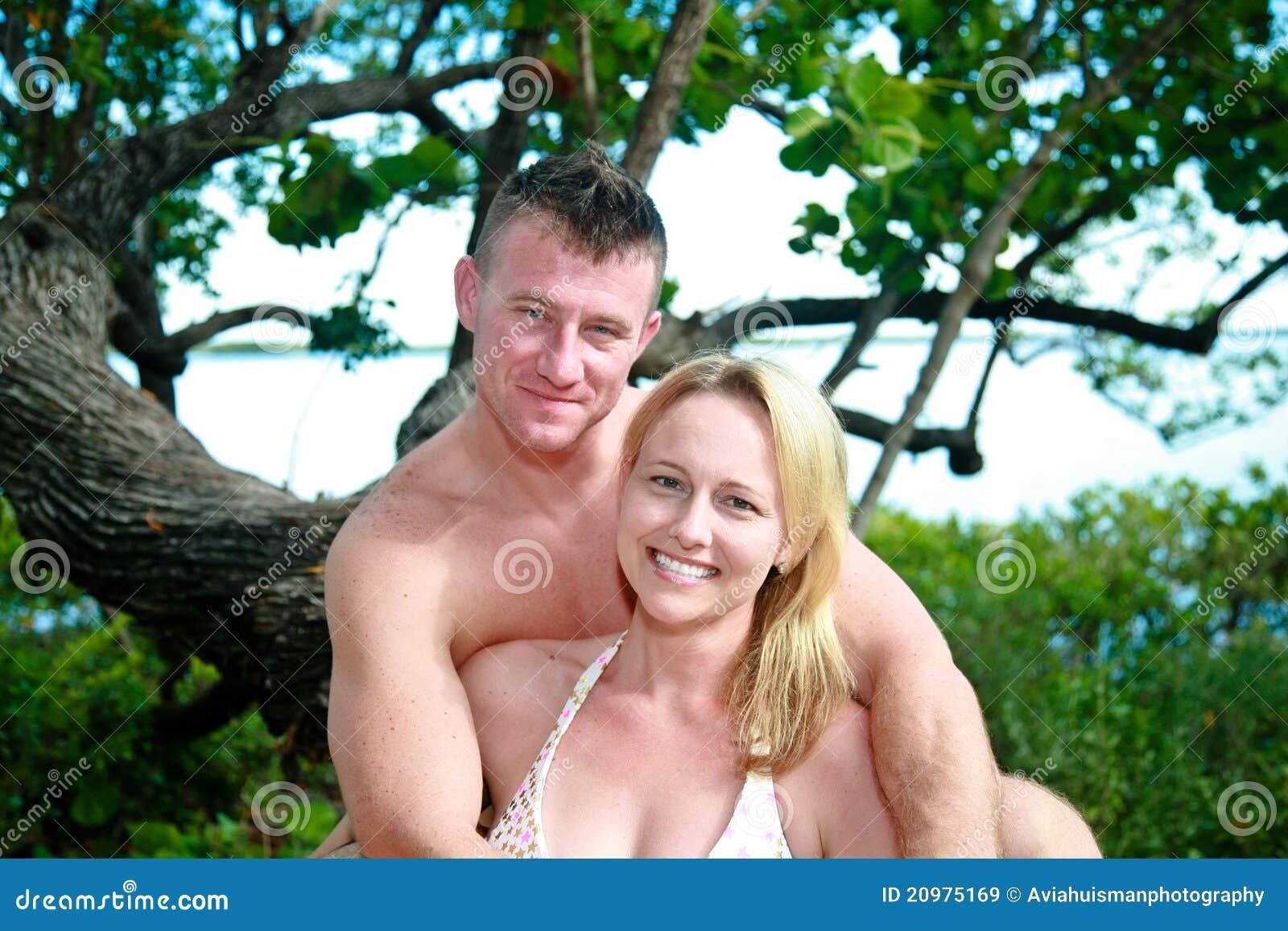 Attraktive Paare, die den Strand genießen