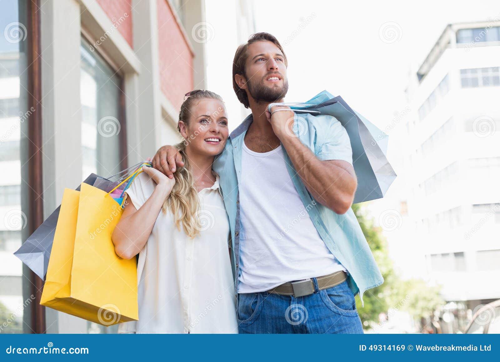 Attraktive Paare, die Einkaufstaschen halten