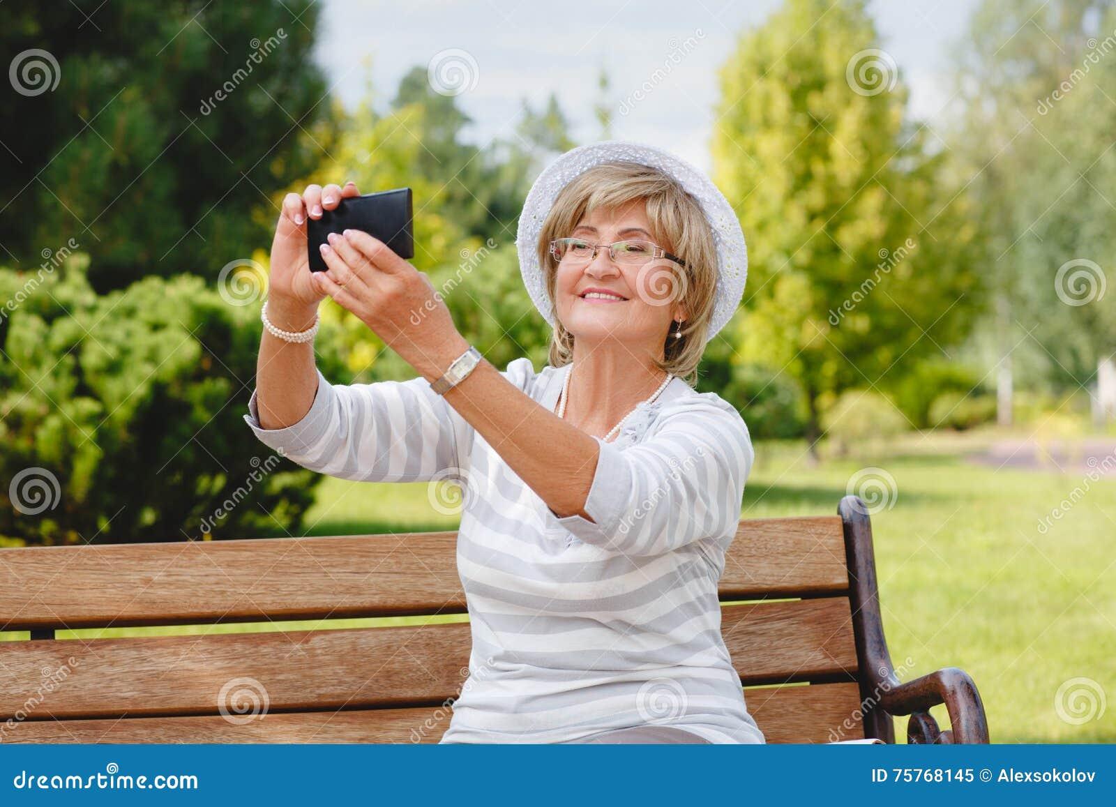 Attraktive Reife Frau, Die Smartphone In Einem Park
