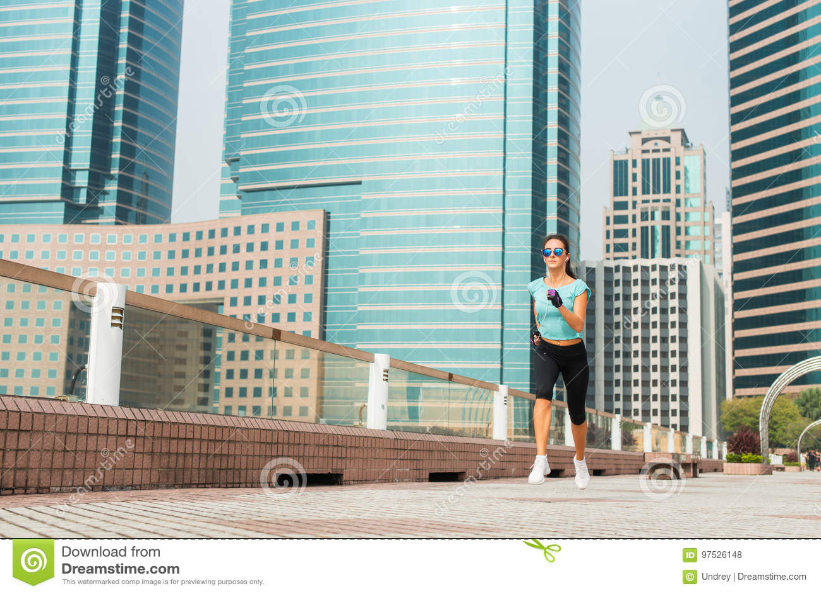 Attraktive sportliche junge Frau, die auf Pflasterung läuft