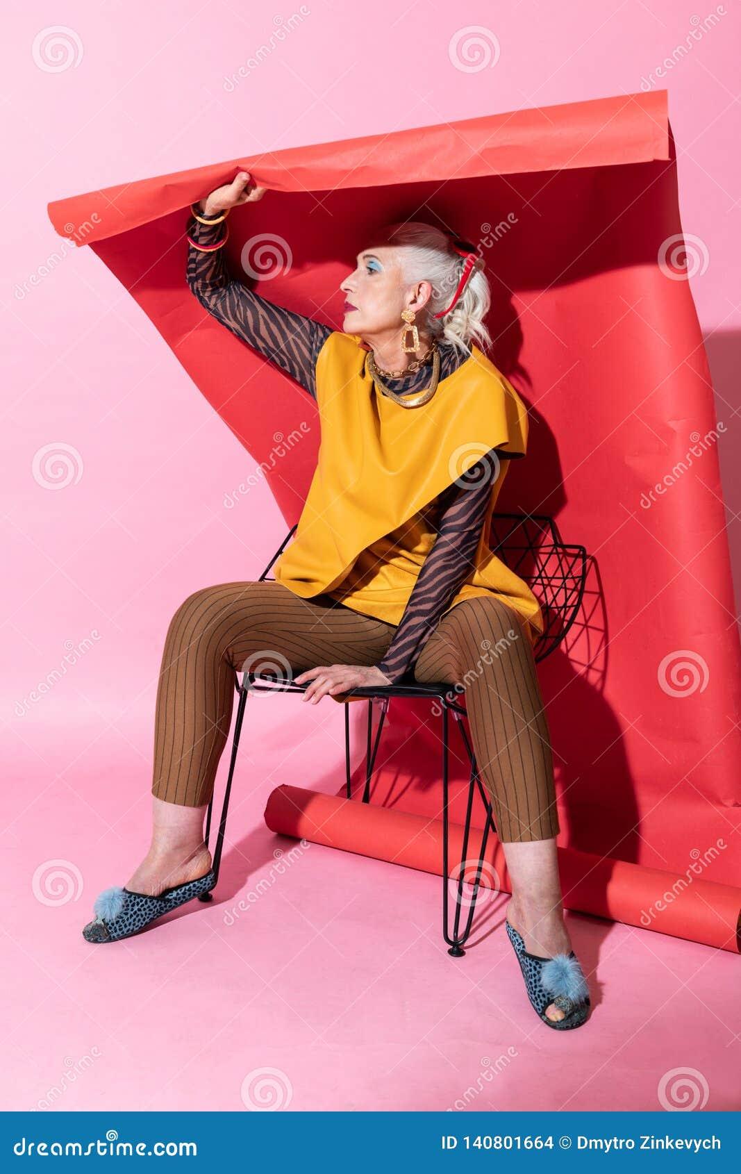 Attraktive weibliche Person, die über rotem Hintergrund sitzt
