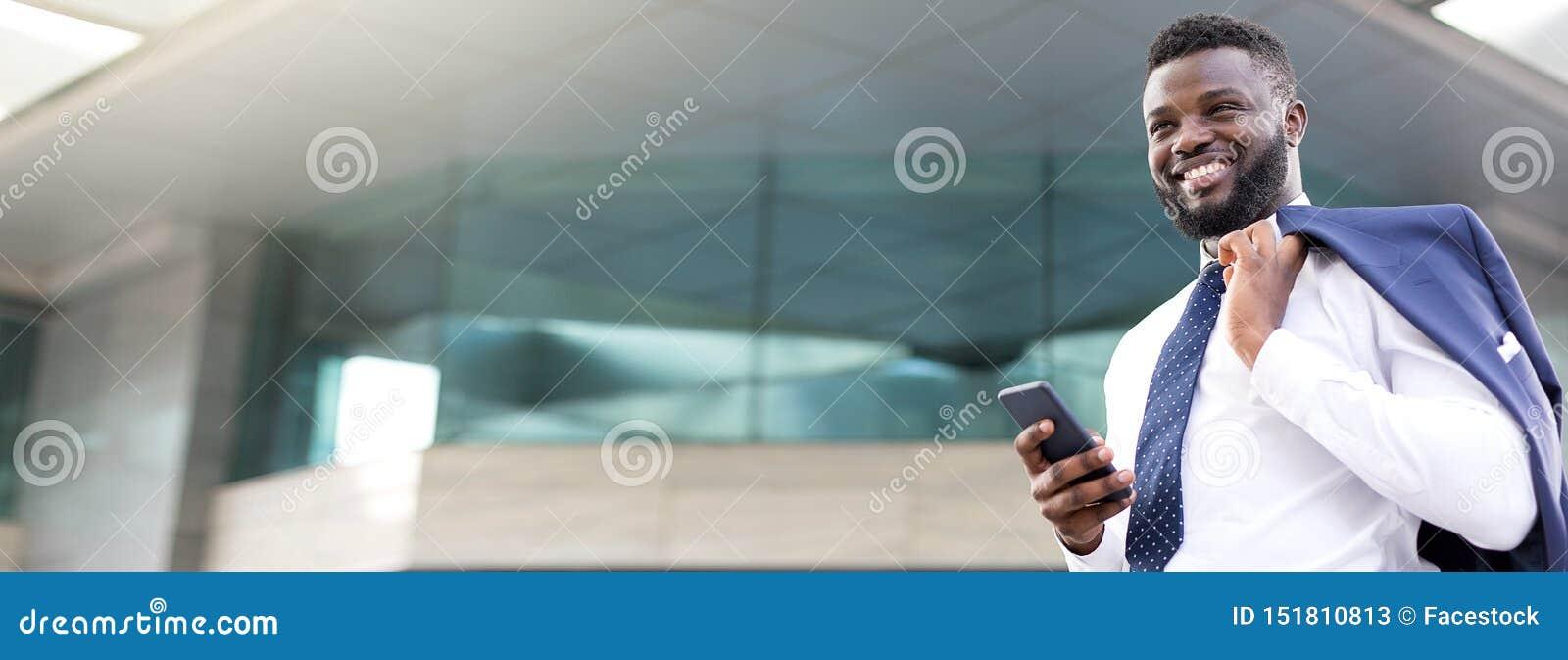 Attraktiver afrikanischer Geschäftsmann, der sein Telefon bei der Stellung nahe einem Vollgeschoss und gerade nach vorn schauen h