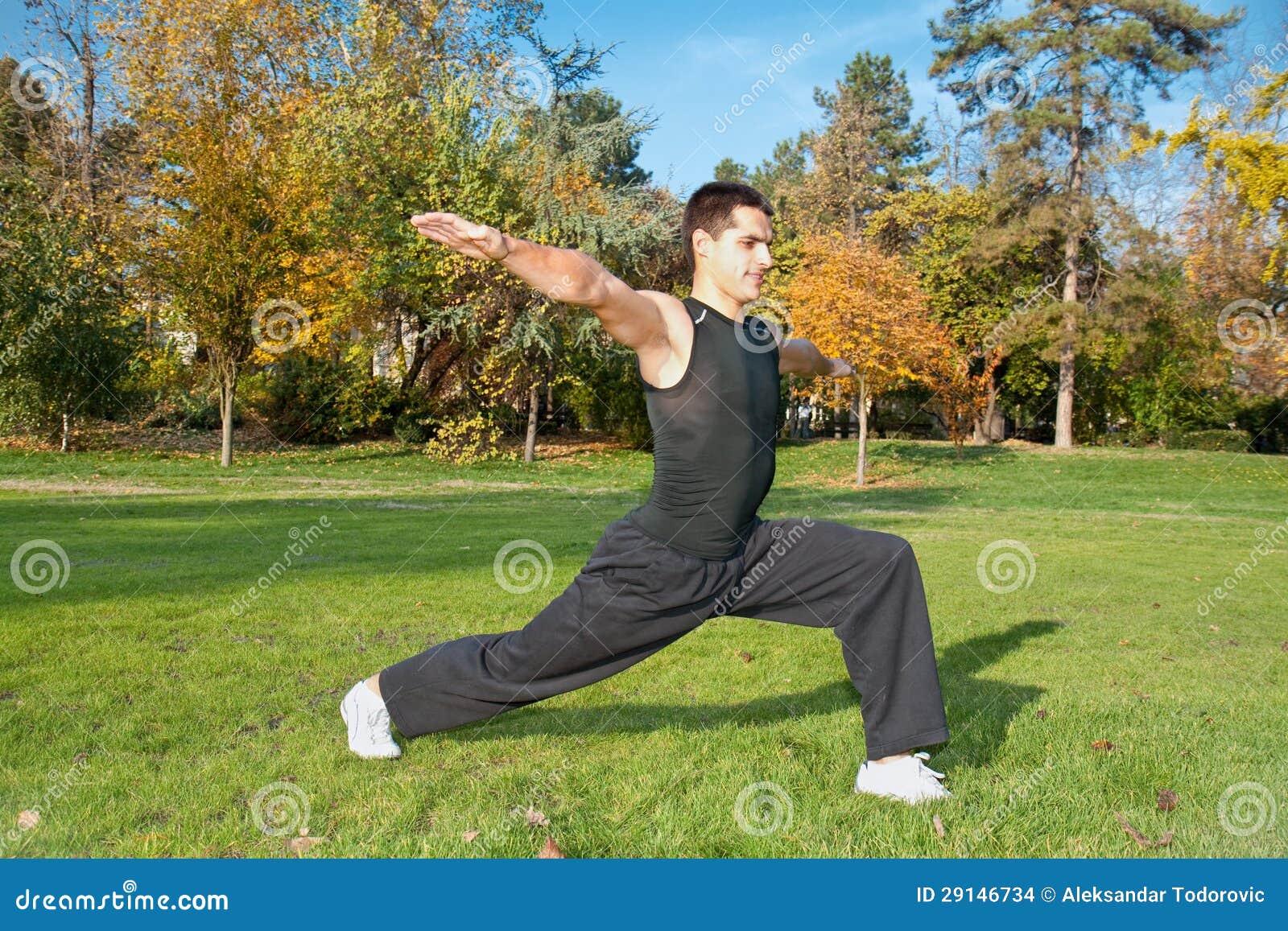 Attraktiver junger Mann, der Übung im Park tut