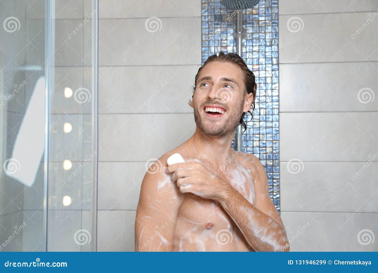 Attraktiver junger Mann, der Dusche mit Seife nimmt