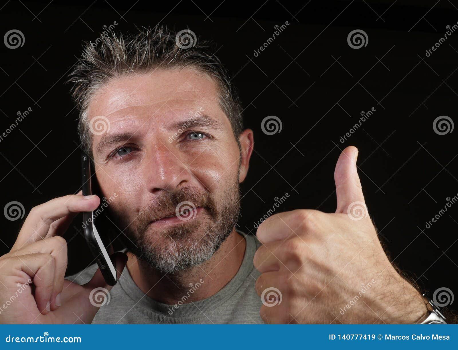 Attraktiver kaukasischer Mann, der am Handy hat das Geschäftsgespräch lokalisiert auf dem schwarzen Hintergrund aufgibt Daumen he