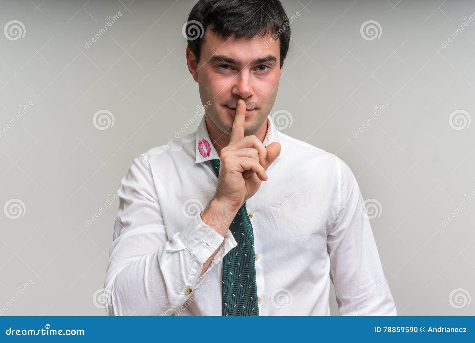 Attraktiver Mann mit dem Finger auf Lippen und Lippenstift am Hemdkragen
