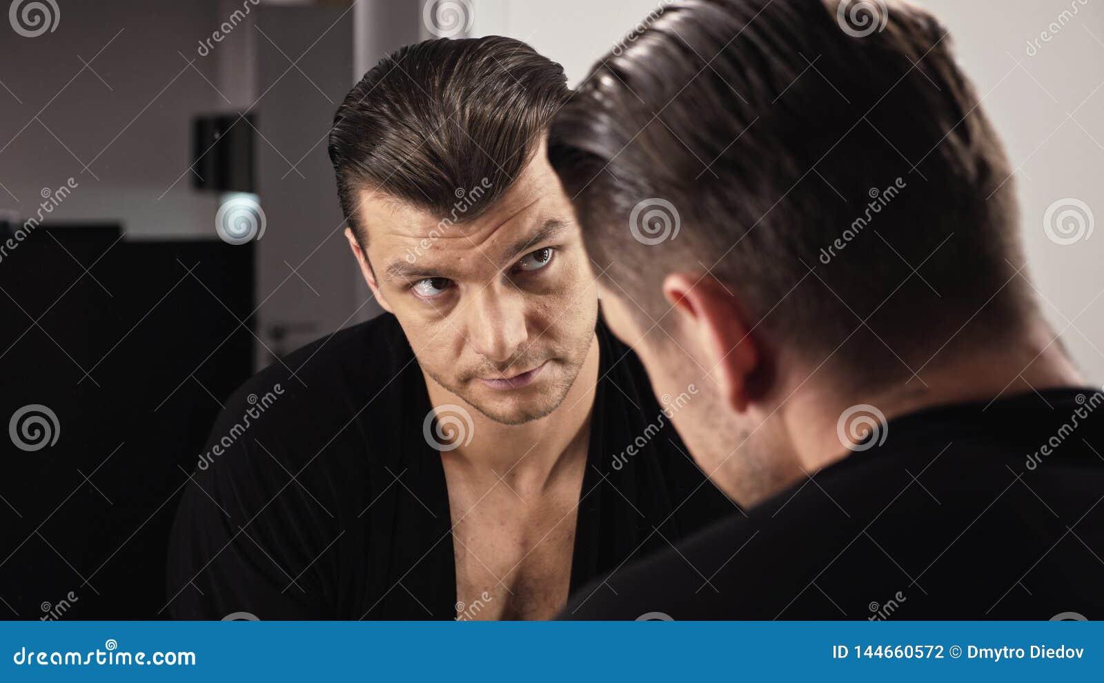 Attraktiver Mann vor einem Spiegel in einem schwarzen Hemd ?berpr?ft sich