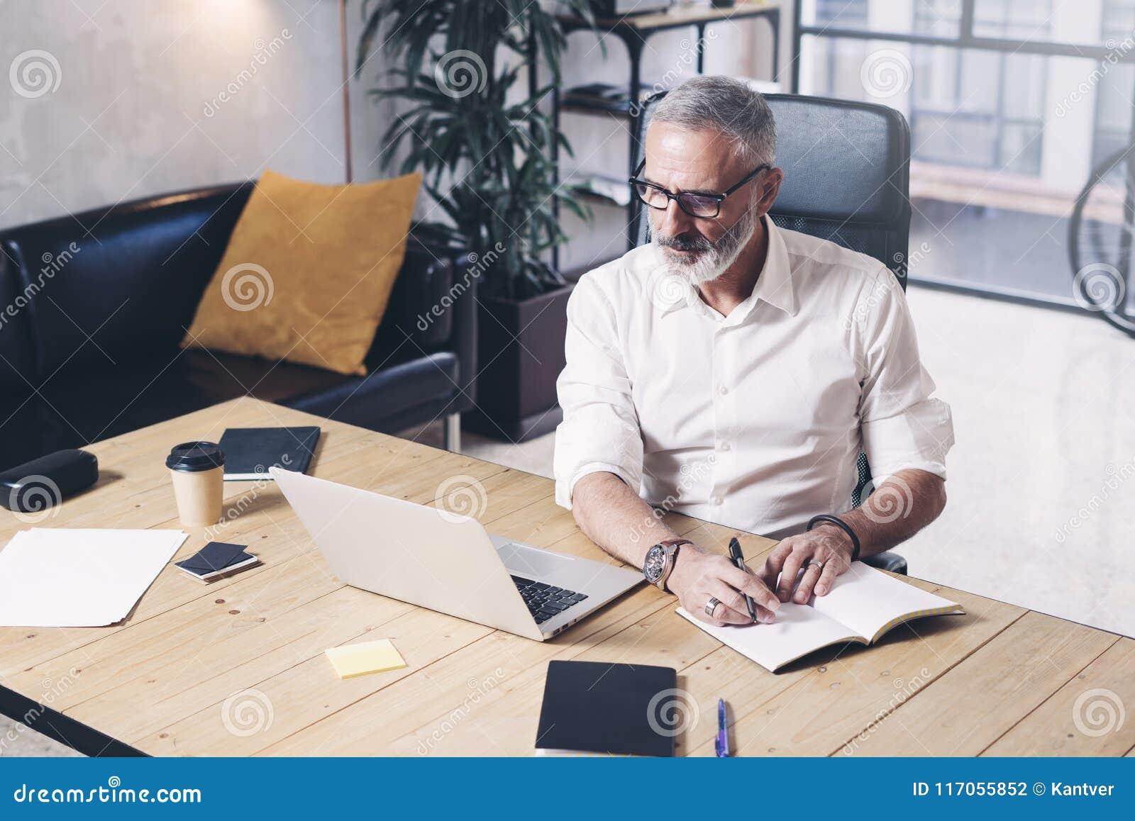 Attraktiver und vertraulicher erwachsener Geschäftsmann unter Verwendung der beweglichen Laptop-Computers und der Herstellungsanm